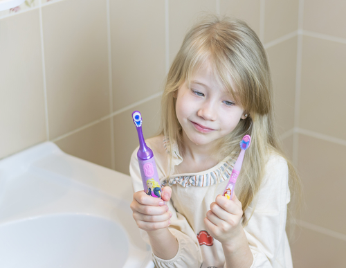 The girl compares electric and conventional toothbrushes.